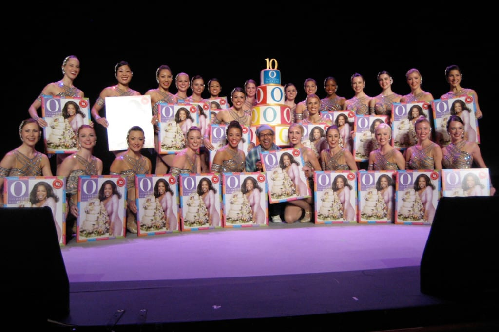 The Rockettes with their cardboard cutouts of the 10th Anniversary edition of O, The Oprah Magazine.